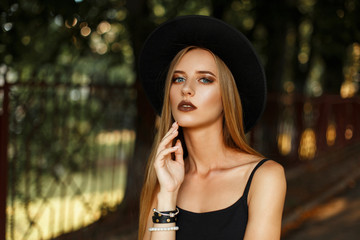 Beautiful young woman with makeup in black stylish clothes and a fashionable hat in the street