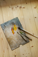 Wooden palette with oil paints yellow red, brushes and palette knife over wooden floor. Top view with space. Art concept. Atmospheric day light