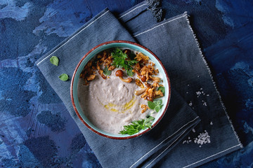 Mushroom cream soup in ceramic bowl served with forest mushrooms, greens, fried onion on blue textile napkin over dark blue texture concrete background. Top view with space