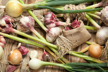Fresh vegetables, garlic and onions on a rustic wooden background. View from above.
