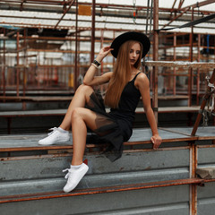 beautiful fashionable woman in a black hat and a stylish skirt in white shoes sits on a metal table