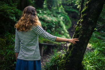 Woman resting her hand on a tree in the forest