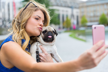 young woman with a pug makes a selfie