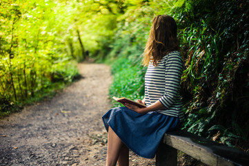 Woman erading on bench in forest