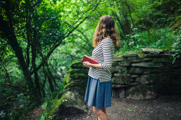 Woman with book standing in the forest