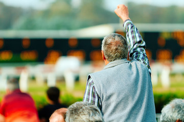 Gambler celebrates with his hand up on a racetrack