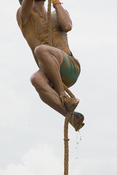 Detail of men´s body covered by mud climbing a rope during spartan race.