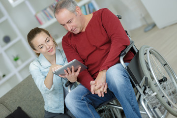 young carer and senior man using tablet