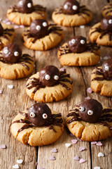 Halloween food: shortbread cookies with chocolate spiders close-up. vertical background