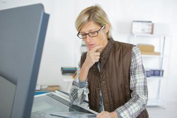 mature female technician searching cause of machine failure