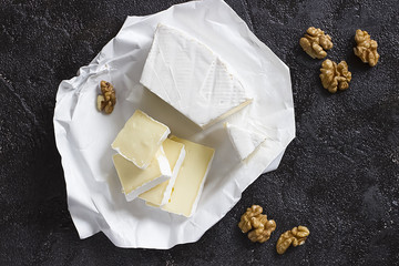 Camembert or brie cheese in white paper and walnut  on black  background.
