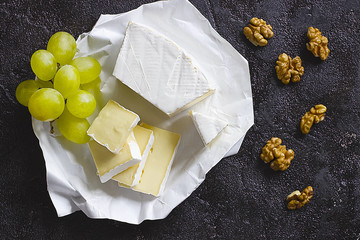 Camembert or brie cheese in white paper, walnut and green grape on black  background.