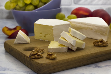 Camembert or brie cheese on a wooden board, green grapes and red nectarines