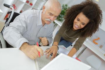 senior man and young woman smiling and looking at laptop