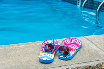 sunglasses and flip-flops by swimming pool