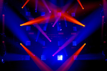 Stage lights of different colors, background of glowing blue and red spotlights