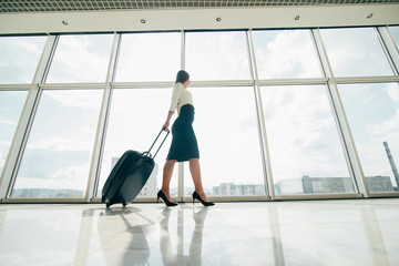 Business woman with laggage bag walking in airport to gate