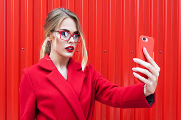 young woman with red lips taking picture on smartphone self-portrait, screen view, over red background