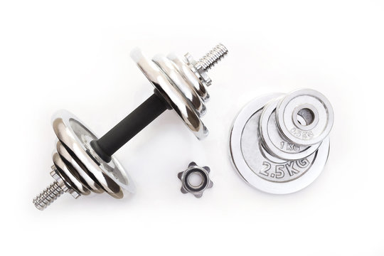Top view of an adjustable metal dumbbell with a set of extra plates on white background.