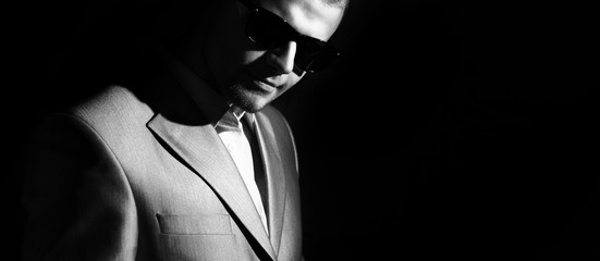 portrait of business men in sunglasses, low key on the black background,  black and white photo