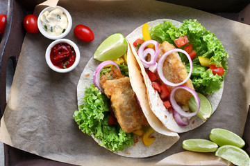 Wooden tray with delicious fish tacos on kitchen table
