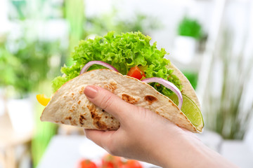 Woman holding delicious fish taco in kitchen