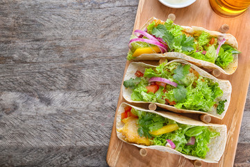 Wooden holder with yummy fish tacos on kitchen table