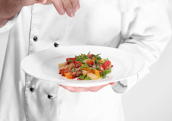 Young male chef holding plate with salad on light background