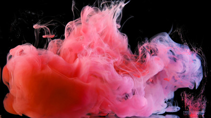 Real shot color paint drops in water. Ink swirling underwater. Cloud of ink collision isolated on black background. Colorful abstract smoke explosion. Close up view