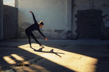 Beautiful ballerina dancing in abandoned building