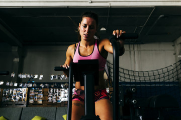 Concentrated woman working out on exerciser