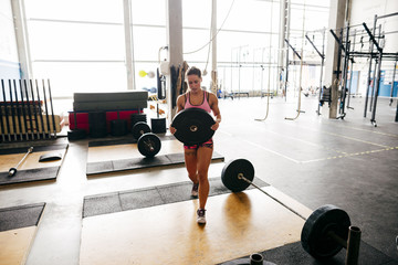 Girl carrying weights in gym