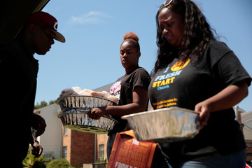 Clesha Love, center, and her mother, Demetria Jackson, of Fresh Start Community Church, deliver food and water to victims of the flood in the aftermath of Hurricane Harvey in Houston
