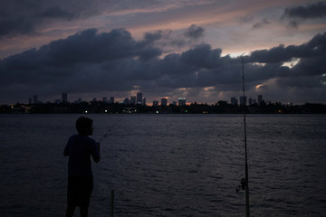 The Miami skyline is seen in the background as a boy fishes ahead of the arrival of Hurricane Irma in Miami Beach, Florida
