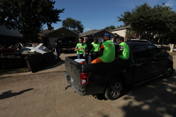Volunteers from BAPS charities leave a neighborhood after spending the day helping a homeowner clean his home in the aftermath of tropical storm Harvey in Katy