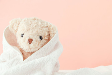 Teddy bear covered by a towel on pink pastel background,Cute teddy bear covered towel after bath