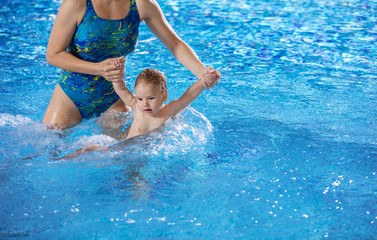 Young woman and little son in swimming pool