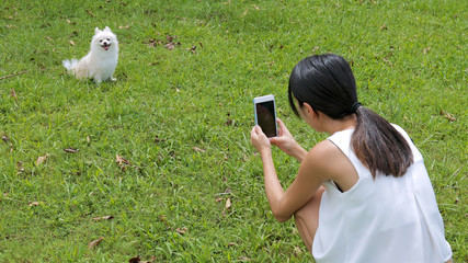Woman taking photo with cellphone on her dog