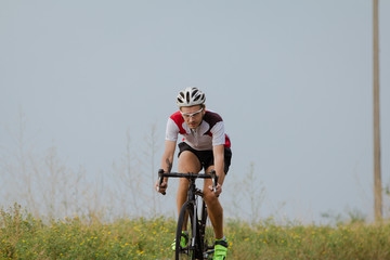 Bicycle racer in helmet and sportswear training alone on empty country road, fields and trees background