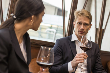 Businessman and Woman Talking for Business while Drinking red wine in Bar, People with Business concept.