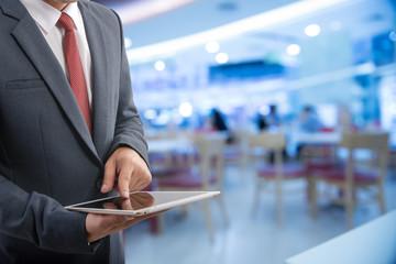 Businessman on blurred background holding tablet