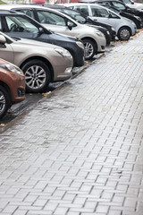 lots of cars parking in the city street on rainy day