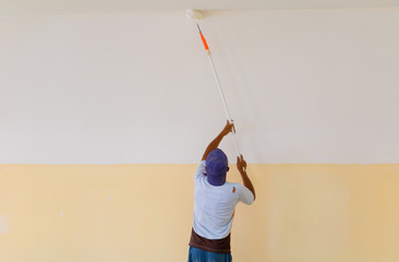 painter use paint roller on wall empty room with copy space add text