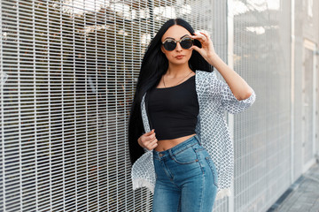 Vogue model woman in stylish fashion clothes with vintage sunglasses near the wall of the grid
