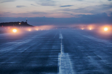 Empty runway at airport during a foggy evening