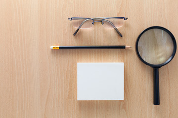 business objects of pencils,white paper note,magnifying glass,and glasses on wooden office desk for business background and design.