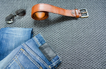 Blue jeans, men's leather rolled belt and black sunglasses on gray background
