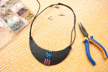Assembly of bib black necklace. Making jewelry from polymer clay with beads and pliers. Working craft process.