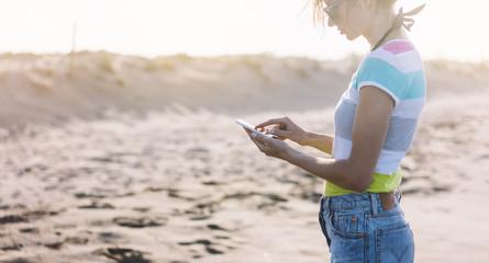 Hipster girl hold on smart phone gadget in sun sand coastline. Traveler using in female hand mobile on background beach seascape horizon flare. Tourist look on sun ocean, summer lifestyle