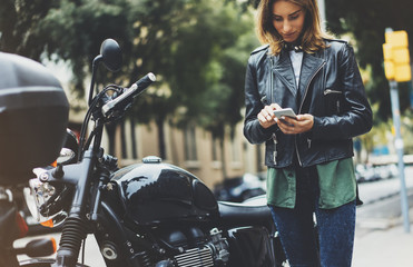 Fotomurales - Girl in leather jacket holding smart phone on background motorcycle in sun flare city, hipster using in female hands and texting mobile, motorbike street lifestyle, tourist planing route in summer